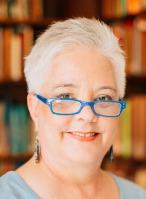 Sheila Athens cropped blue glasses books behind.jpg