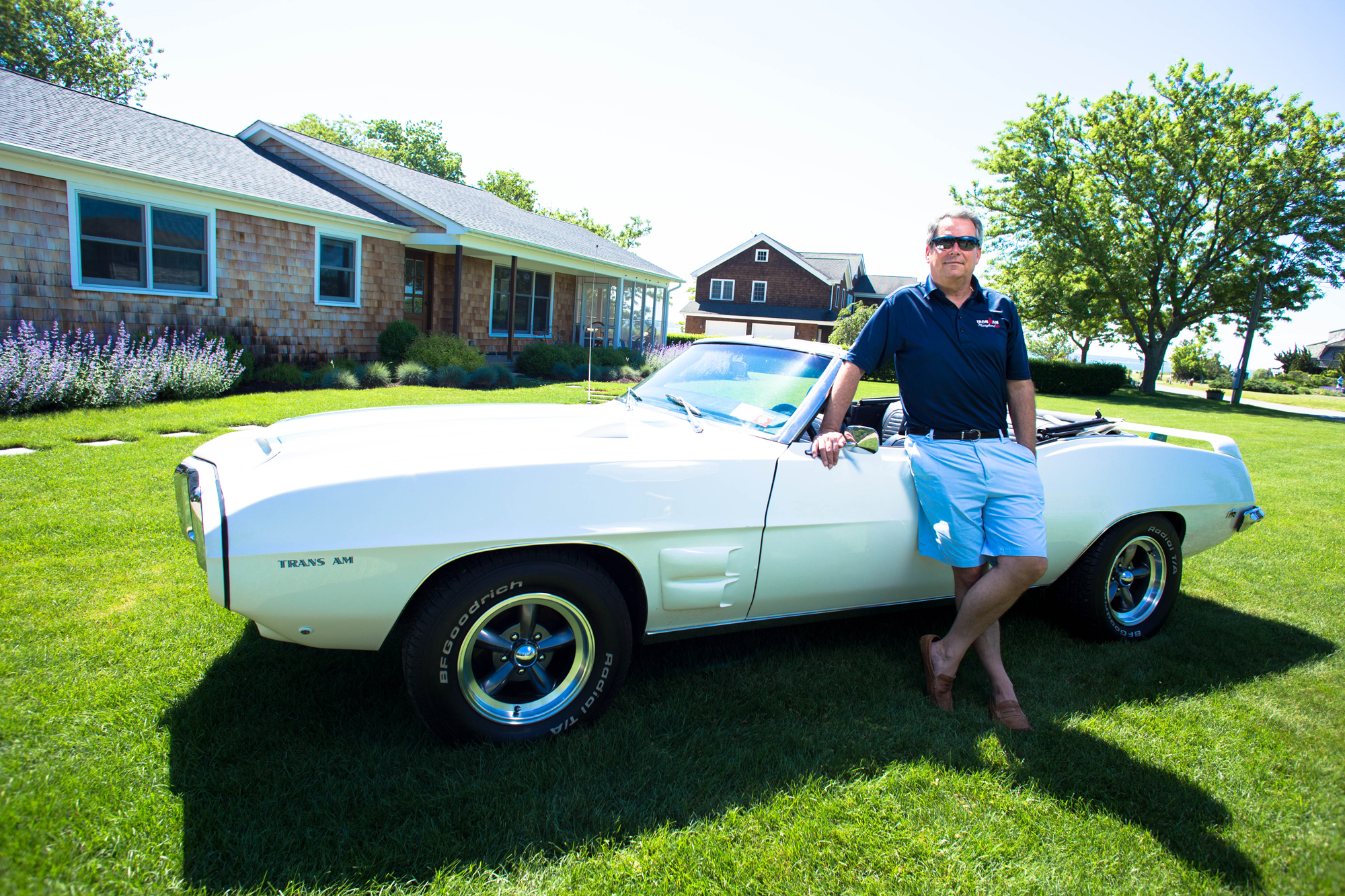 Kevin leaning against a white vintage car parked on grass with a house in the background.