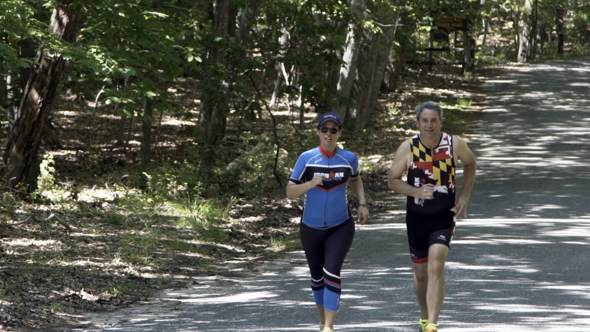 Kevin and training partner running along a tree lined road, in training for triathlons.