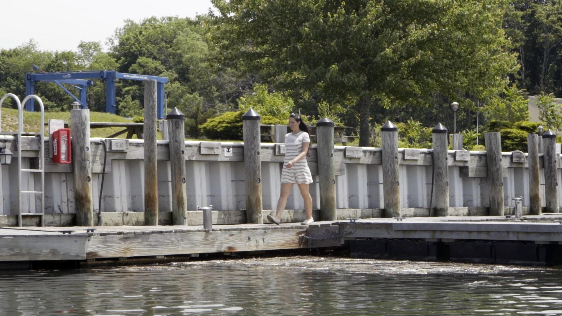 A woman walking along a dock in front of a bulkhead.
