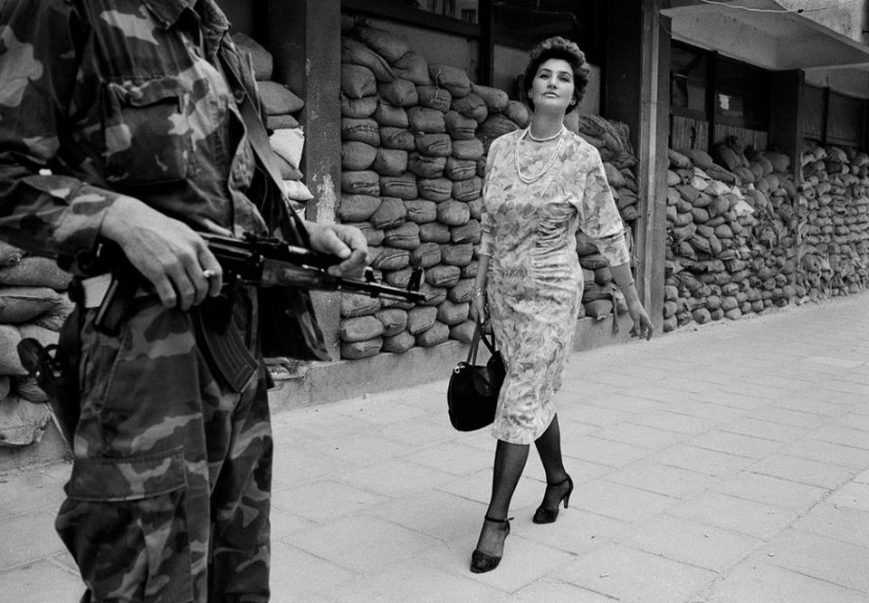 """SARAJEVO, BOSNIA - 1995: In the dangerous suburb of Dobrinja, Meliha Varesanovic walks proudly and defiantly to work during the Siege of Sarajevo, 1995. Her message to the watching Serb gunmen who surround her city is simple, """"you will never defeat us."""" Tom Stoddart/Reportage by Getty Images"""
