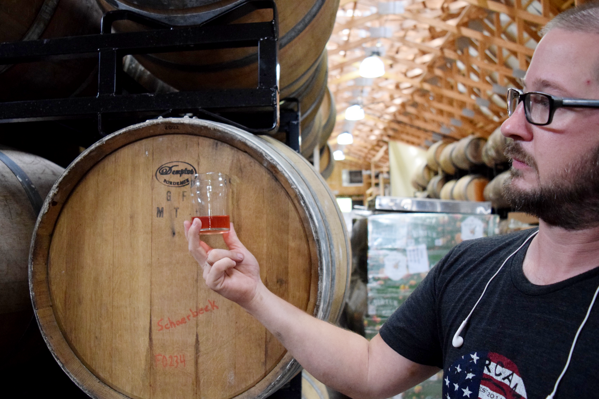 Virtue Cider Head Cidermaker Seth Boeve observes an early version of a small batch of cider with cherries.