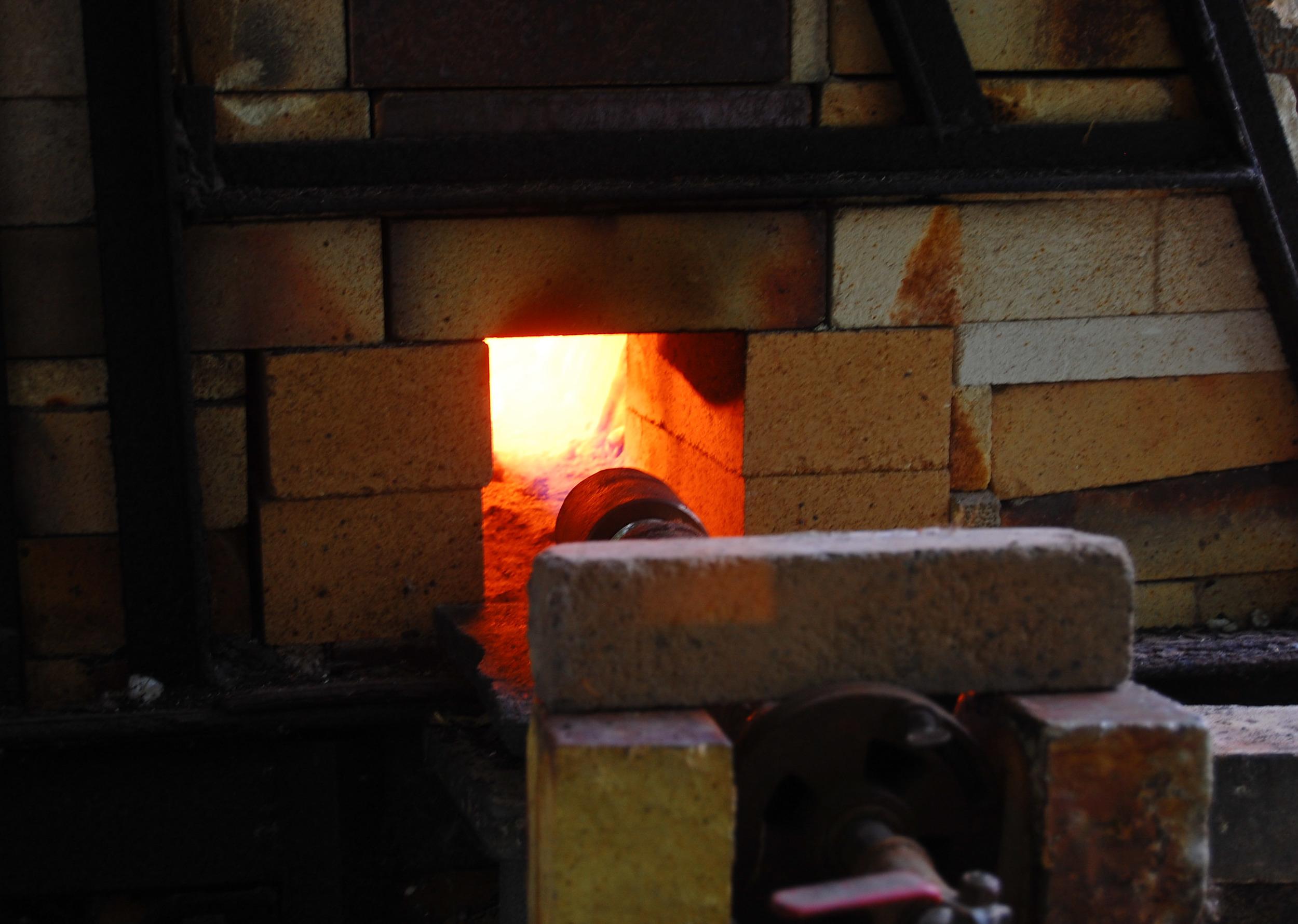Closeup of a kiln burner during firing