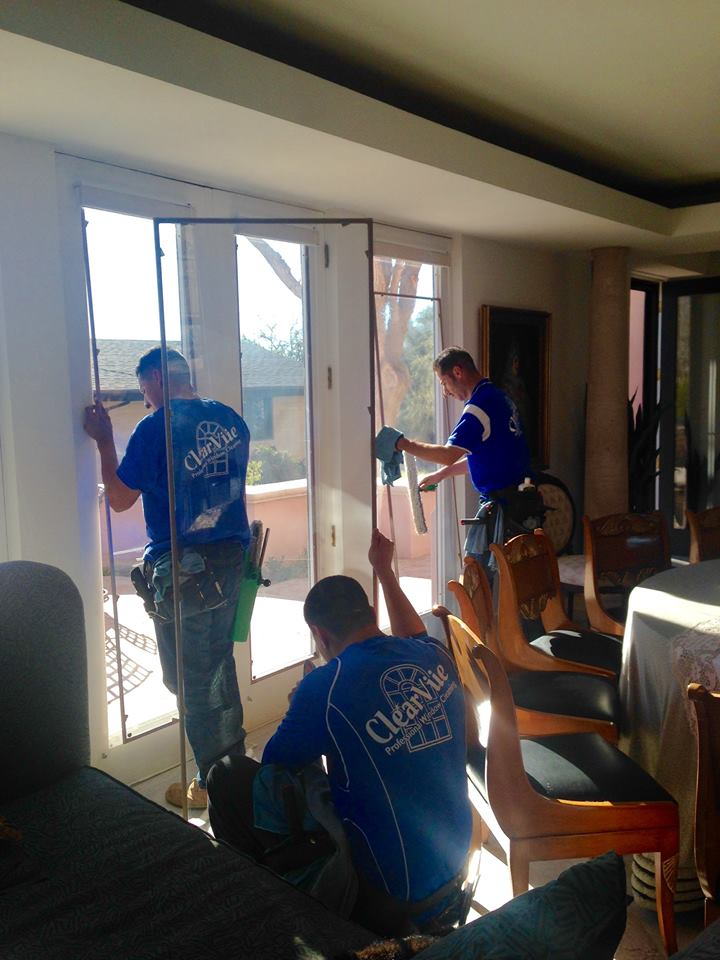 Three employees removing window tint from some french doors in a residential home