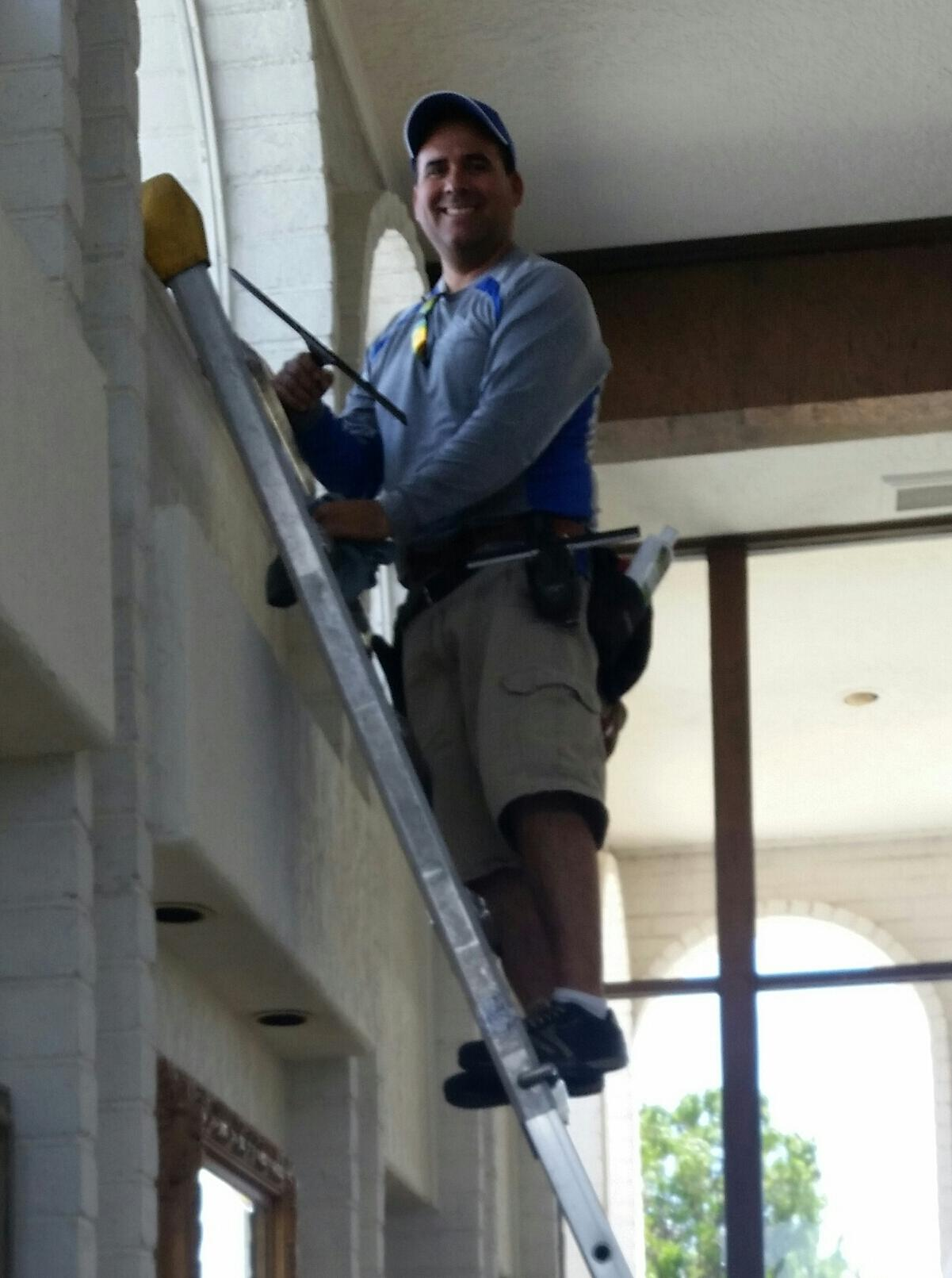 Pete Sanchez, owner on a ladder cleaning a window in a commercial building