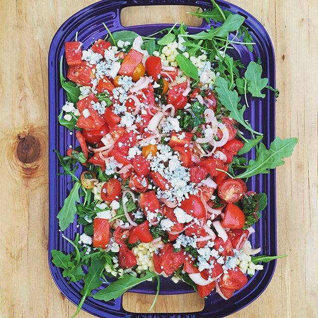 Heirloom Tomato Salad with Charred Corn, Arugula & Blue Cheese. 🍅This salad would be perfect alongside a grilled tri-tip this weekend! We believe summer isn't over until the tomatoes are gone so enjoy the seasons bounty while it lasts! ☀️ Link to recipe in bio. 😎
