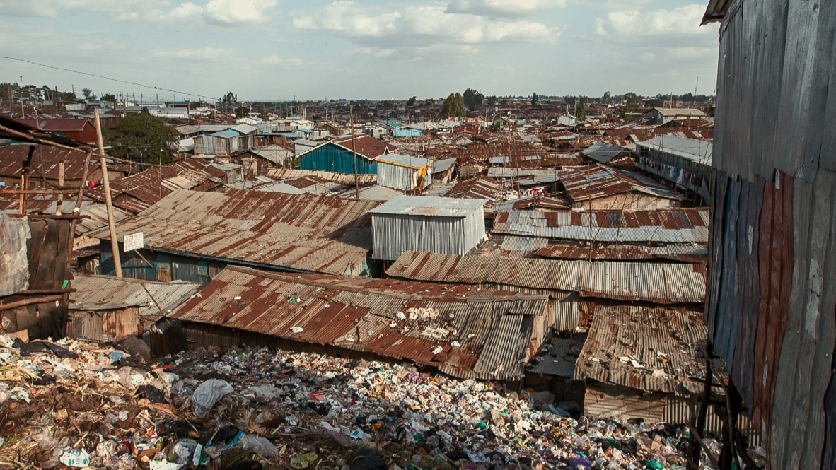 Looking out across the roofs of Kibera, the rubbish, in the foreground, is right up against the wall of houses