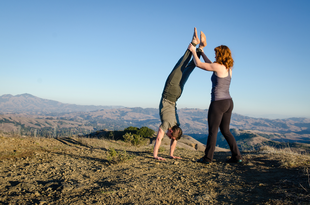 Founders Hannah & Will practicing friend-assisted handstands
