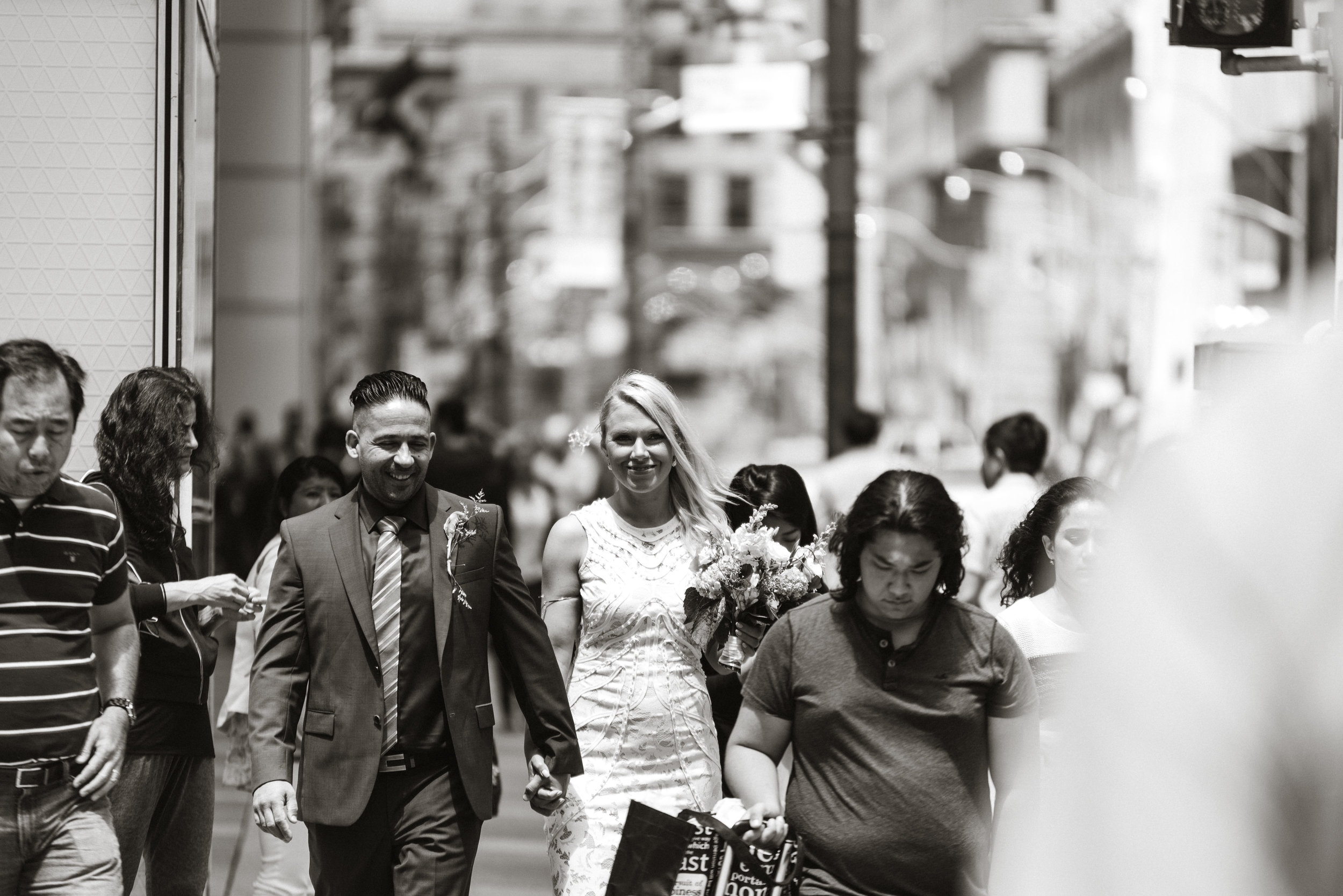 Classic downtown black and white couple crossing toronto street after getting married