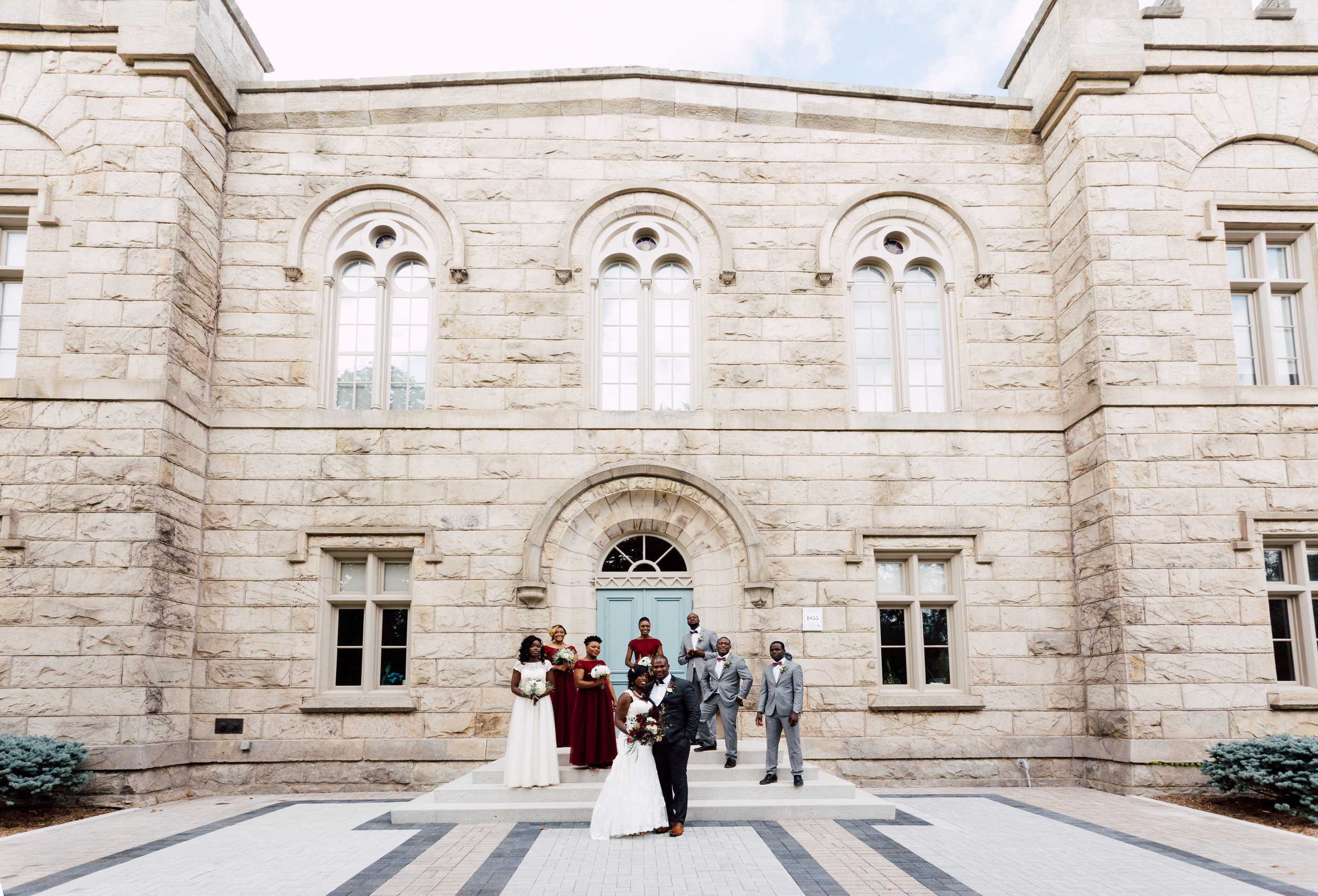 Married couple and bridal party in front of a mansion in toronto
