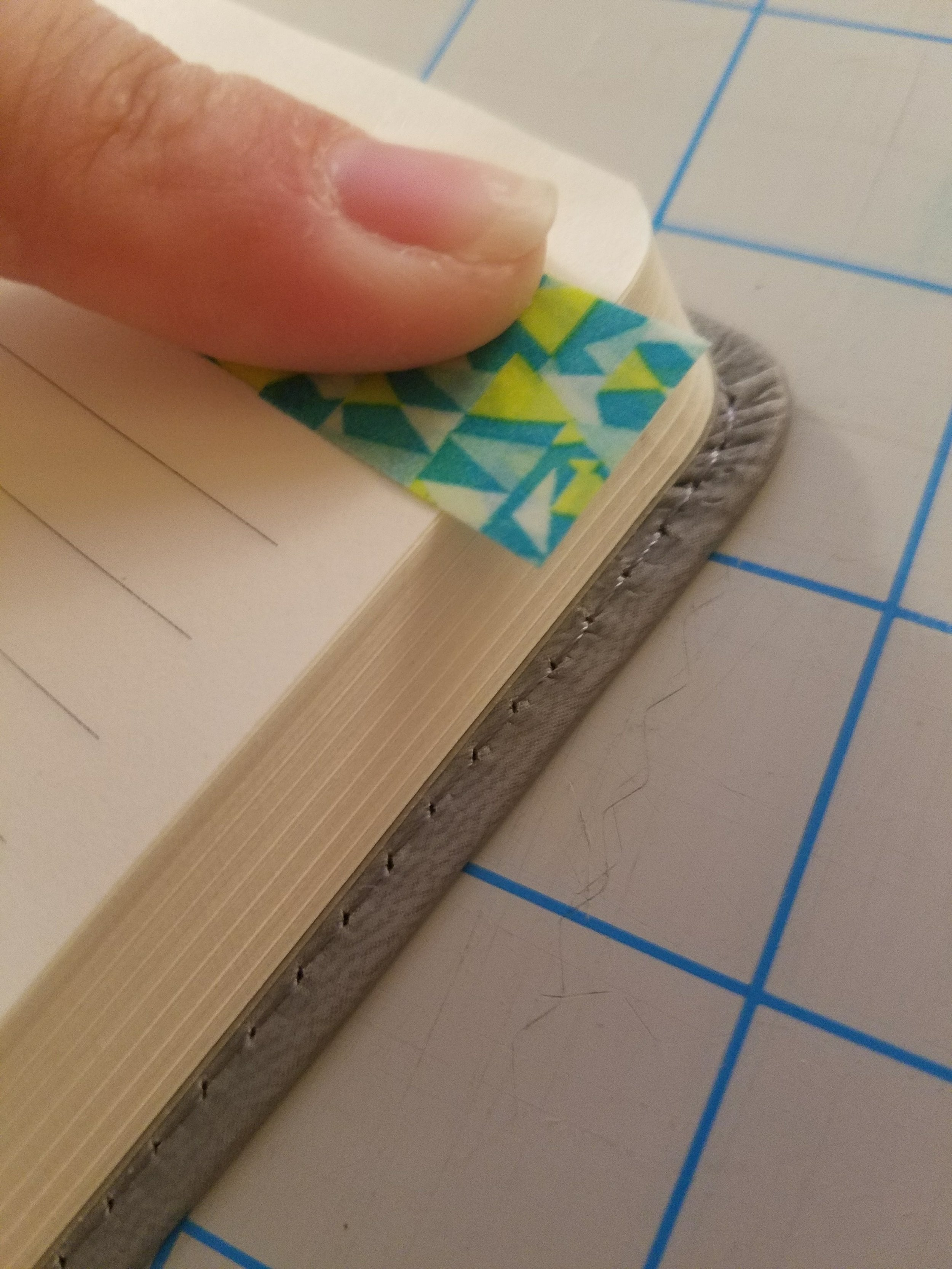 """Take a piece of Washi tape approximately 1.5"""" long and fold about a 1/3 of it in half so that it sticks to itself. Then take the remaining sticky part and attach to the page."""