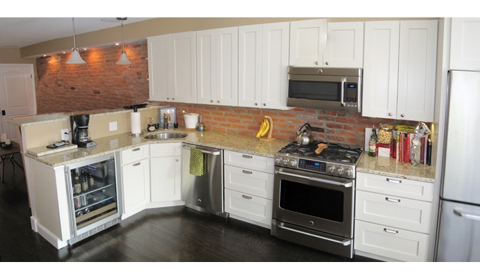 The kitchen, open to the rest of the first floor, continues the exposed brick theme