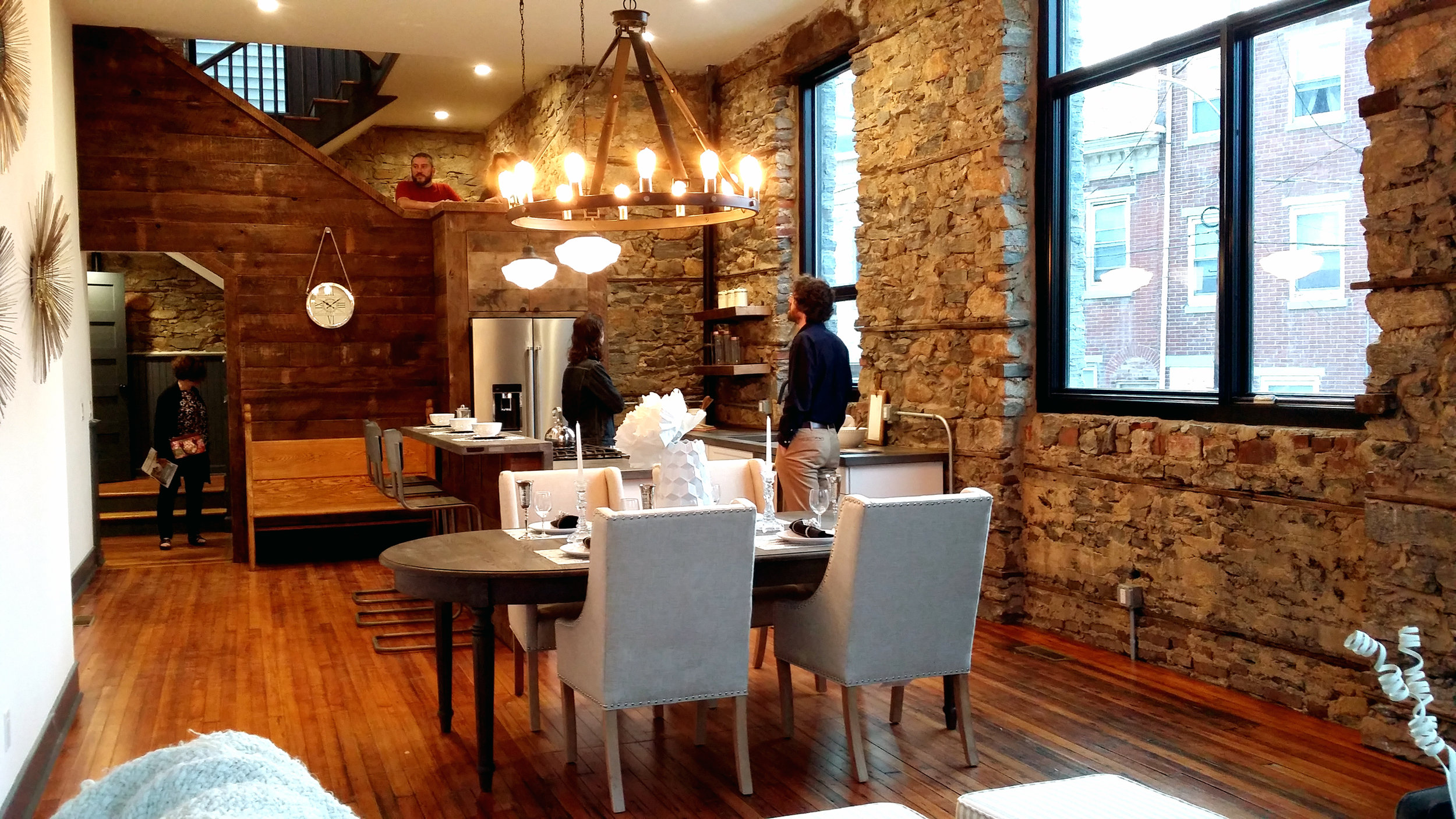 This is the main floor, with kitchen, dining, and living space. The original stone walls are exposed, and the wood floors are original. The wood paneling is salvaged from the original structure.