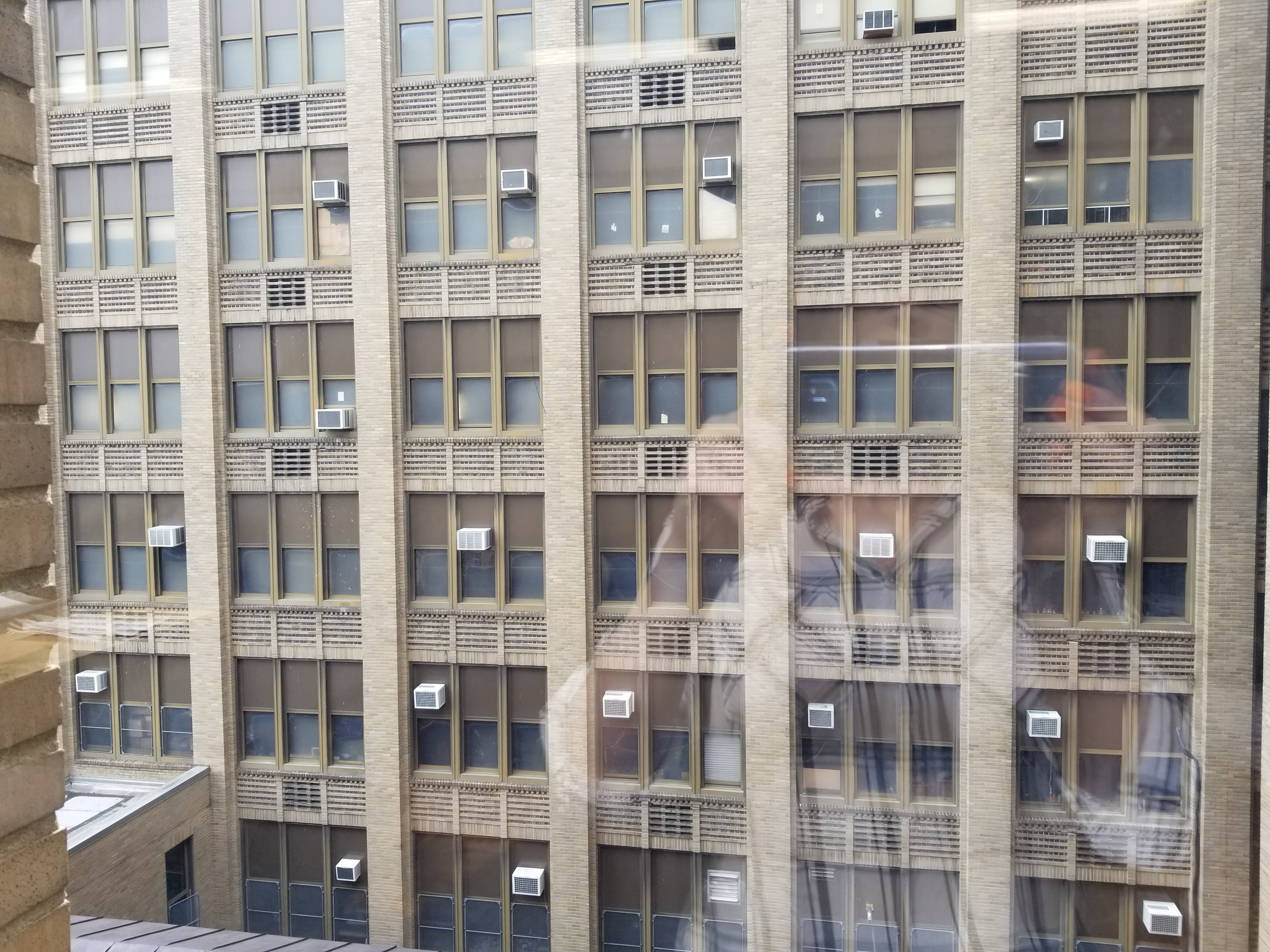 The building has a great rhythm of windows and brick pilasters (and air conditioning units!). You can also see Sara's fun self-portrait reflected in the glass.