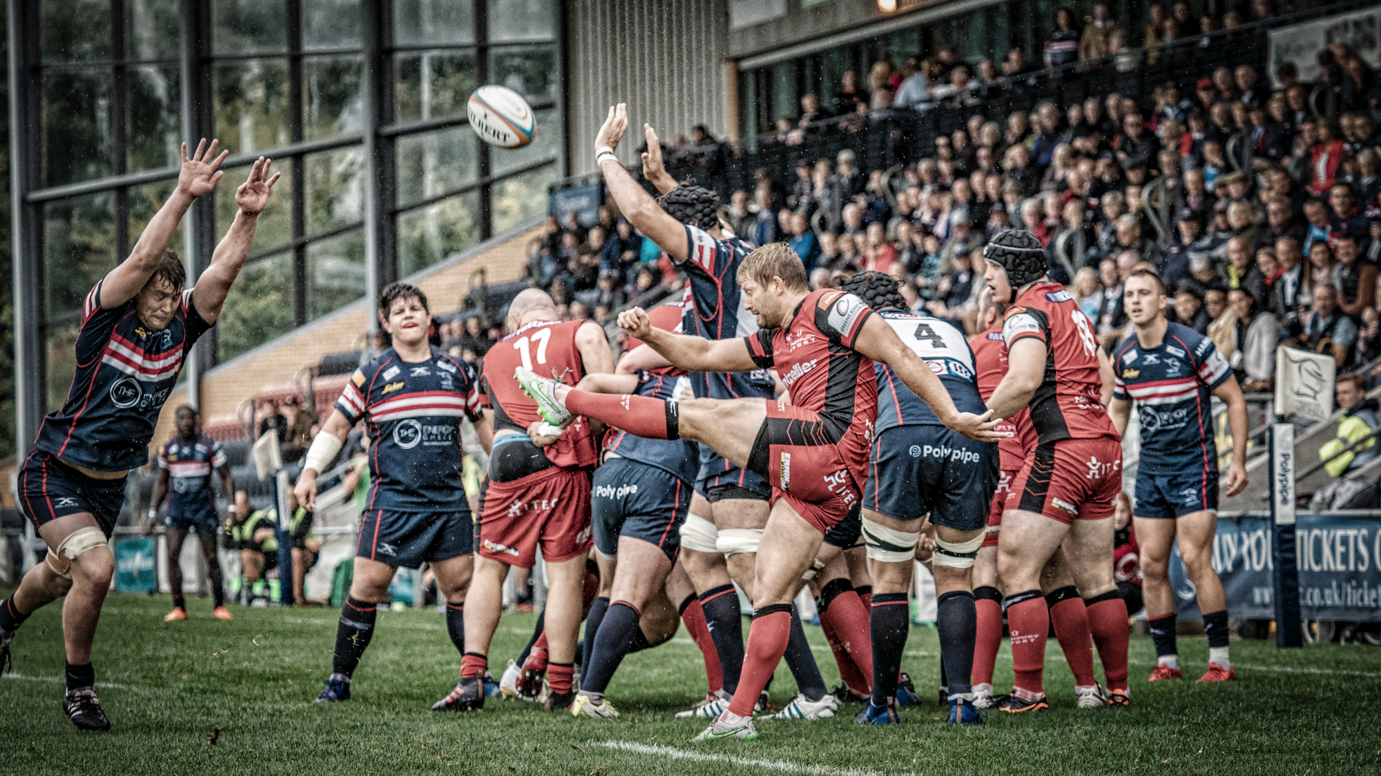 A Hartpury defensive kick with an attentive crowd as backdrop