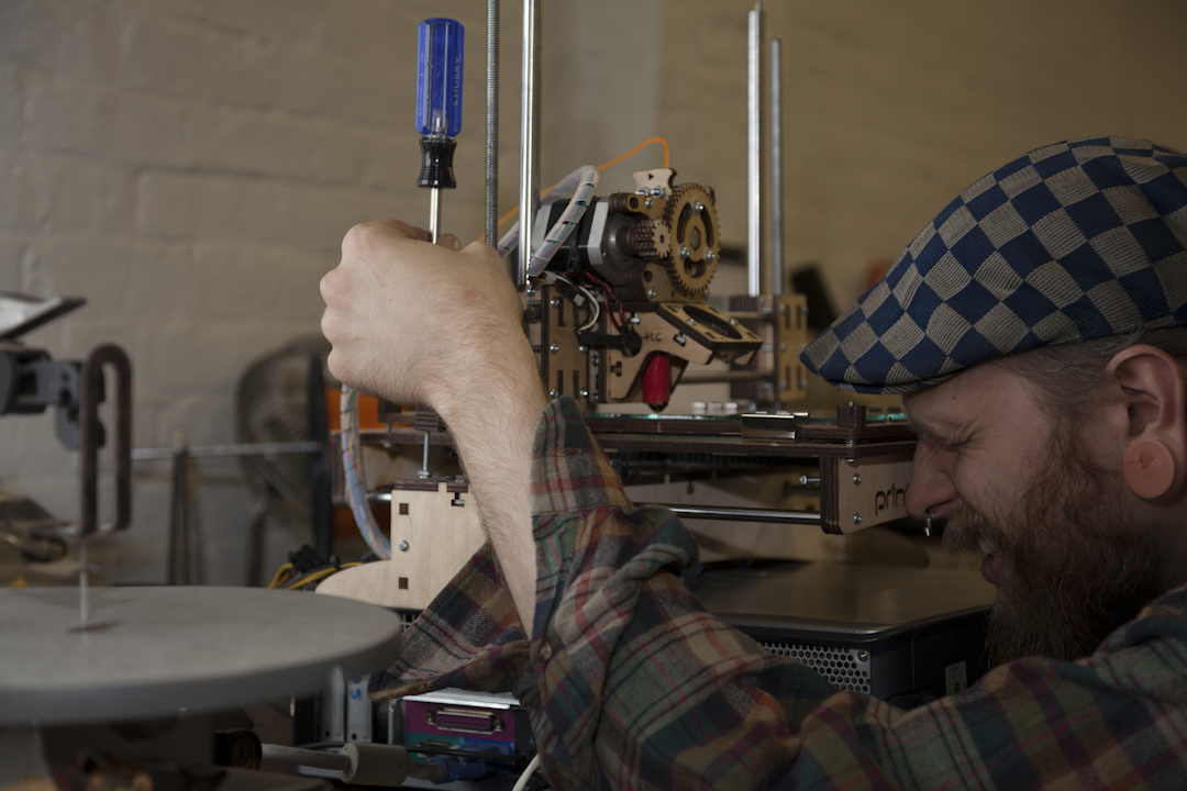Kevin adjusting a 3D printer - photo by Andrew Harrington