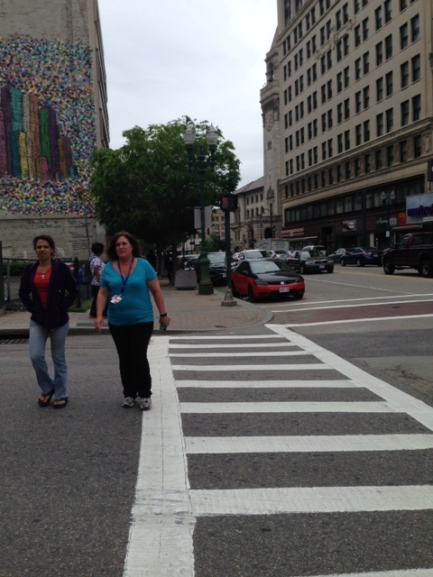 "You can see these walkers on Main Street across from the Hanover Theater crossing Chatham Street.  They waited awhile to get that light after hitting the walking button. In the area that has frequent pedestrian activity such as this, you can have automatic walk intervals to allow pedestrians to cross and make pedestrian activity more predictable.  In fact, if the light on Main Street is green, walkers could have an automatic signal to cross.  Technical terms for this kind of signaling is called, ""concurrent pedestrian phase."" Changing these signals could make a huge impact on the walkability of the city.  Here is one more idea about making walking more pleasant on our city streets.  Let's just stop the current ""Barnes Dance"" pedestrian scrambles.  If you are a walker, you know this kind of signaling.  You press the light, wait and wait until the signal is given and all directions of intersection traffic stop for the pedestrians.  The problem:  Both walkers and drivers are frustrated with the wait they are forced to endure because of  this signaling.  You know the drill.  Press the button.  Wait and wait and wait.  Get impatient.  Try to cross anyway.  Cross.  Light changes.  All cars are stopped but you have already crossed so the traffic in all four directions stop for no reason.  Frustration!"