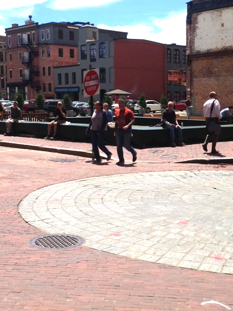 """It looks like a building was taken down here. This was the only """"empty lot"""" we saw on our walk. It seems as if part of the base of the structure has been kept? This area has become a pedestrian plaza and way station with many people sitting under the sun and eating lunch."""
