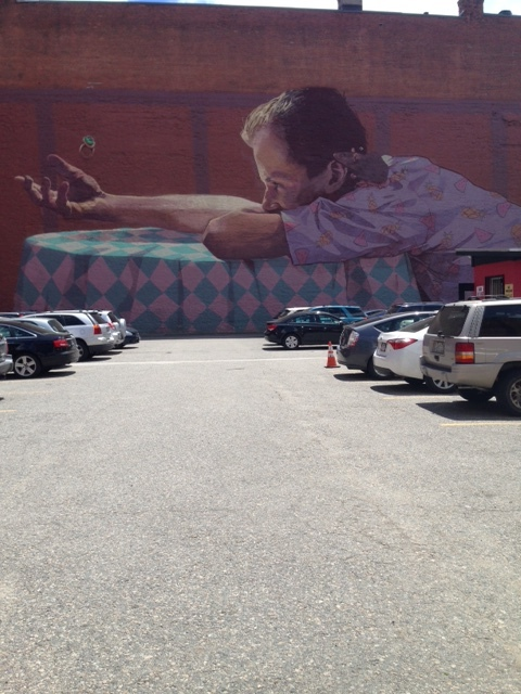 a mural on the outer edge of the neighborhood frames a parking lot