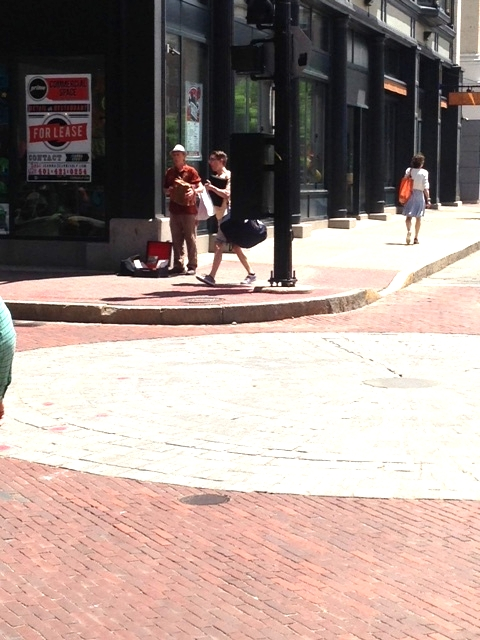 A hint of active street life: A musician plays his accordion on the busy sidewalk.