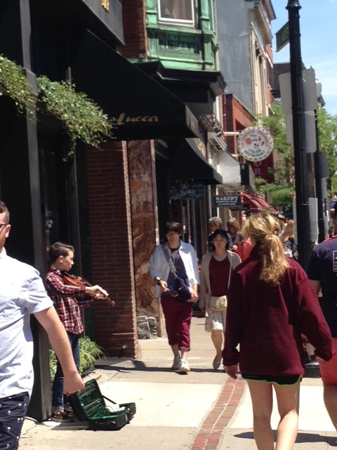 """Streets are crowded with pedestrians. There are so many """"eyes on the street"""" that residents tell us that they are never afraid even walking around at night.Notice the brick trail laying out the route of the Freedom Trail and the young man playing his violin for change."""