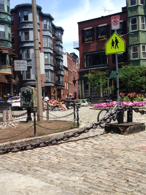 """This photo was taken directly across from the Paul Revere House. This is a neighborhood for walkers and bikers as you can clearly see from the """"no parking"""" sign above the image of walkers and the bicycle tied to the pole below. Check out the sunbathers in the pedestrian plaza in the center of the square and the streets lined with old brick cobblestones. All throughout this dense, mixed use neighborhood, you will see the storefronts on the first floor and the residential units above."""
