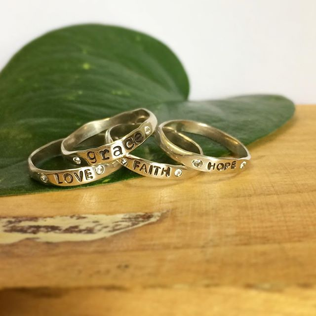"""Just a pile of good things in the studio today! My newly inspired line of rings with your """"word"""" on them flanked by tiny inlaid Swarovski crystals. I have some words that are one stamp: Faith, love, joy, or hope. But for instance, this grace ring is hand stamped individually letter by letter. So if you have a word you need on your finger as a daily reminder.... I can do whatever word you'd like."""