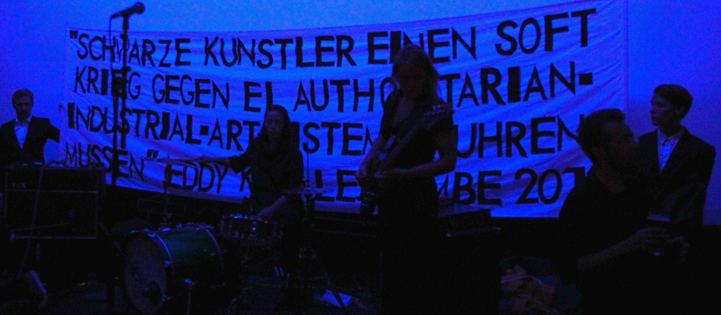 "Our Literal Speed presents ""Our Literal Speed,"" dimensions variable, materials: all-female band playing the main riff from ""Kashmir"" again and again, male models, LGBTQ rights ""propaganda"" banner rendered in art world lingua franca, two-person lecture, 29 August 2013, Bergen Kunsthall, Bergen, Norway (detail)"
