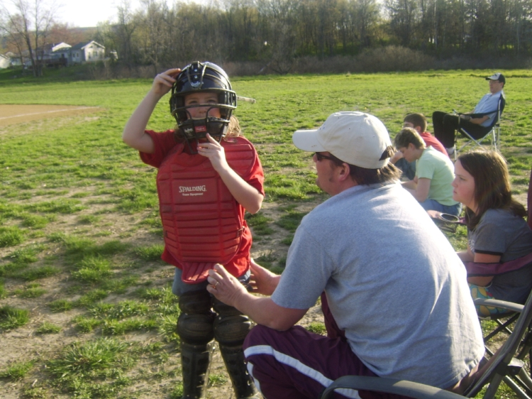 Brian helps Natalie ready for her catcher position in town softball.