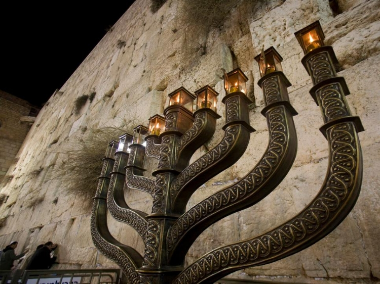 """A Hanukkah menorah (also known as a """"chanukiah"""") glows in front of the Western Wall, Judaism's holiest site, in Jerusalem's Old City. The eight-day festival commemorates the rededication of the Second Temple in Jerusalem during the 2nd century B.C. by Reuters / Ronen Zvulun ( source )"""
