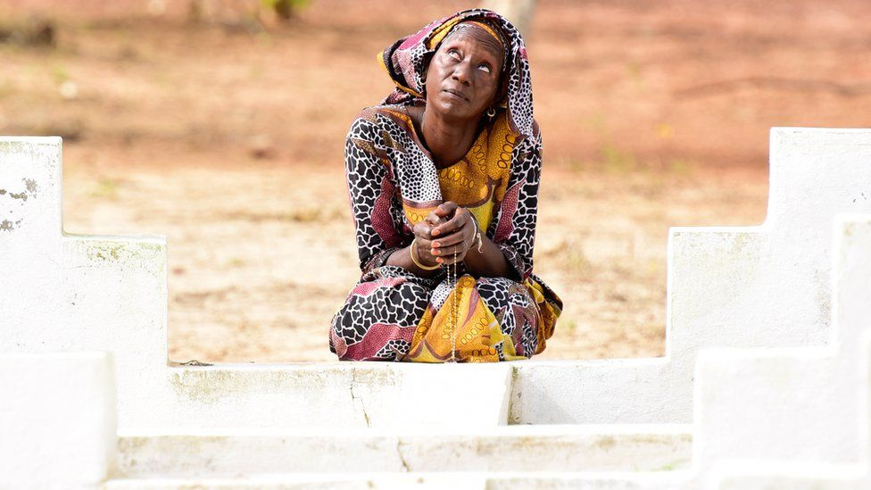 A Senegalese woman kneels in front of a grave to mark the 15th anniversary of the sinking of the ferry, Joola. (2017), AFP/GETTY IMAGES ( source )