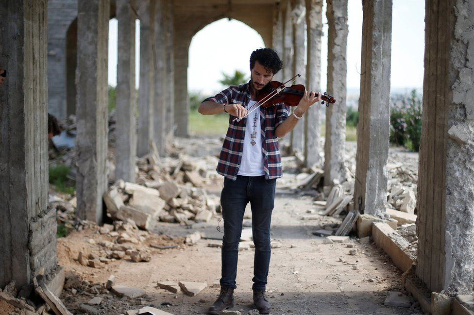 Ameen Mukdad, a violinist who lived under so-called Islamic State for two-and-a-half years, performs at Nabi Yunus, a shrine in eastern Mosul, Iraq, following liberation, 2017. MUHAMMAD HAMED / REUTERS ( source )