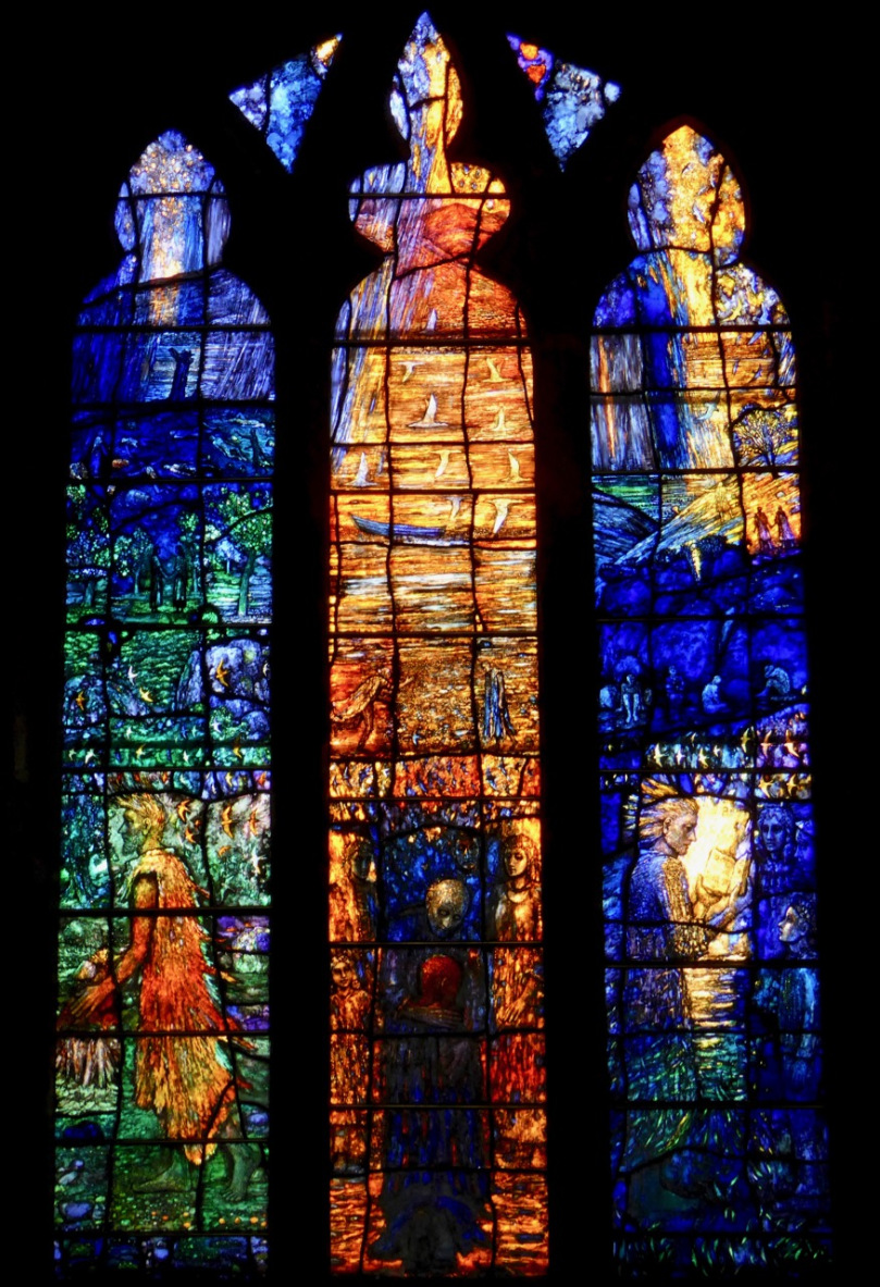 """The theme [of the window] is """"Reconciliation"""", and the central figure is the return of the prodigal son. The right panel is of Jesus reading from the Book of Isaiah and the left is of John the Baptist, patron saint of the church. ( source )"""