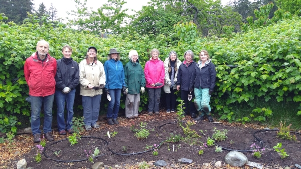 After a rainy morning of transplanting, the Master Gardeners stand behind a beautiful new landscape with big smiles!