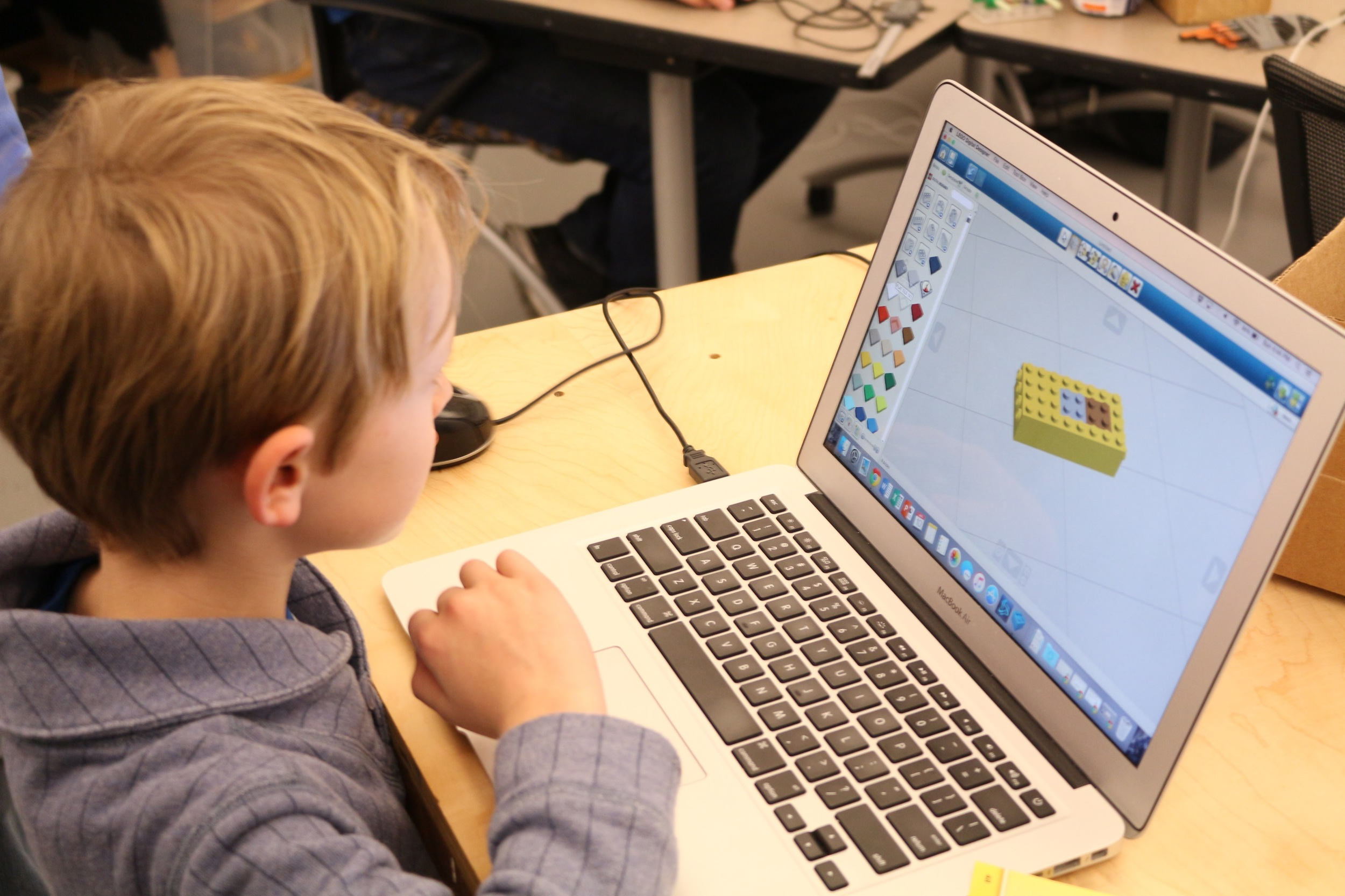 Charlie builds a car in Lego Digital Designer.