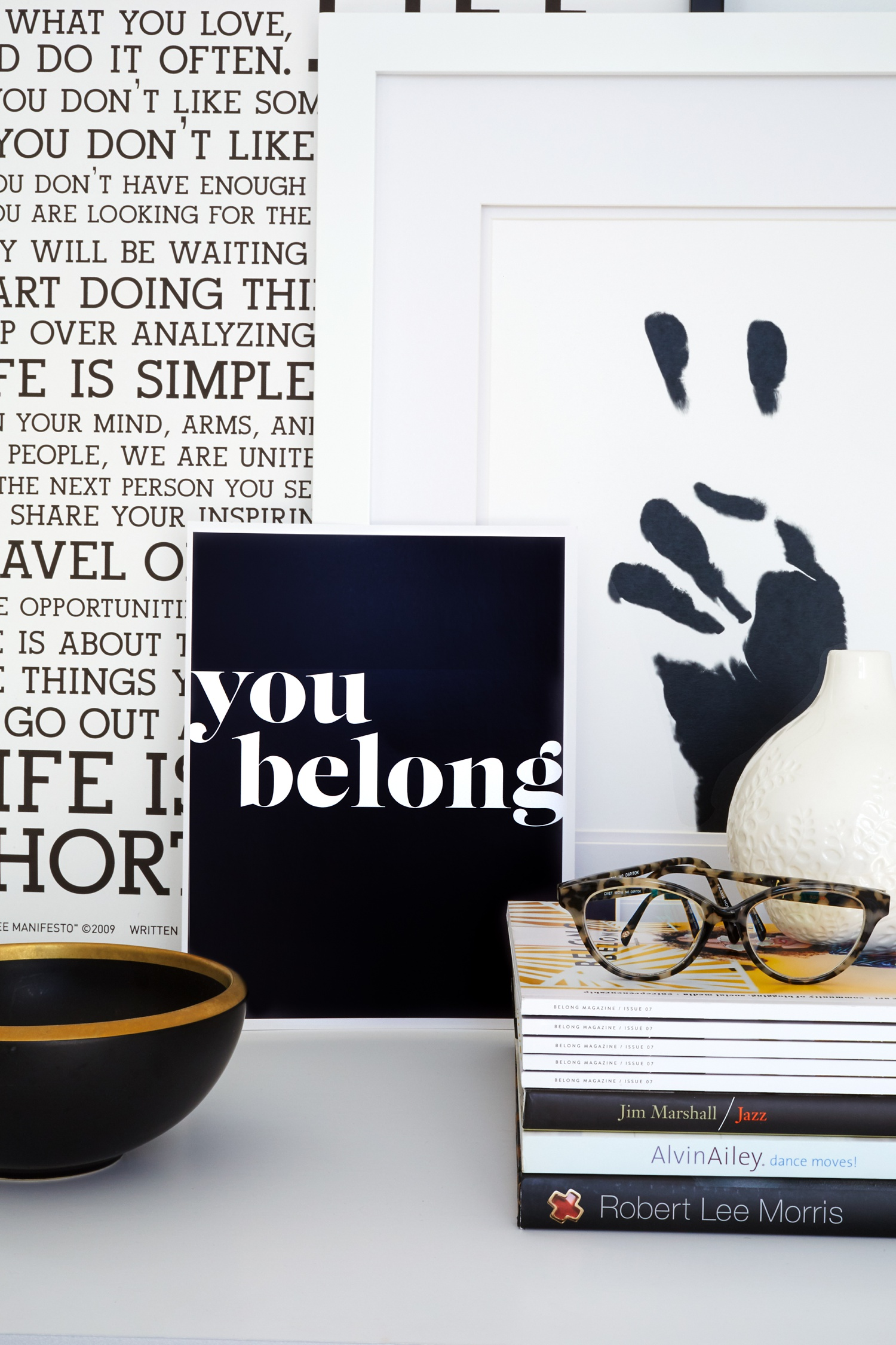 Stack of magazines and books with glasses and Holestee Manifesto