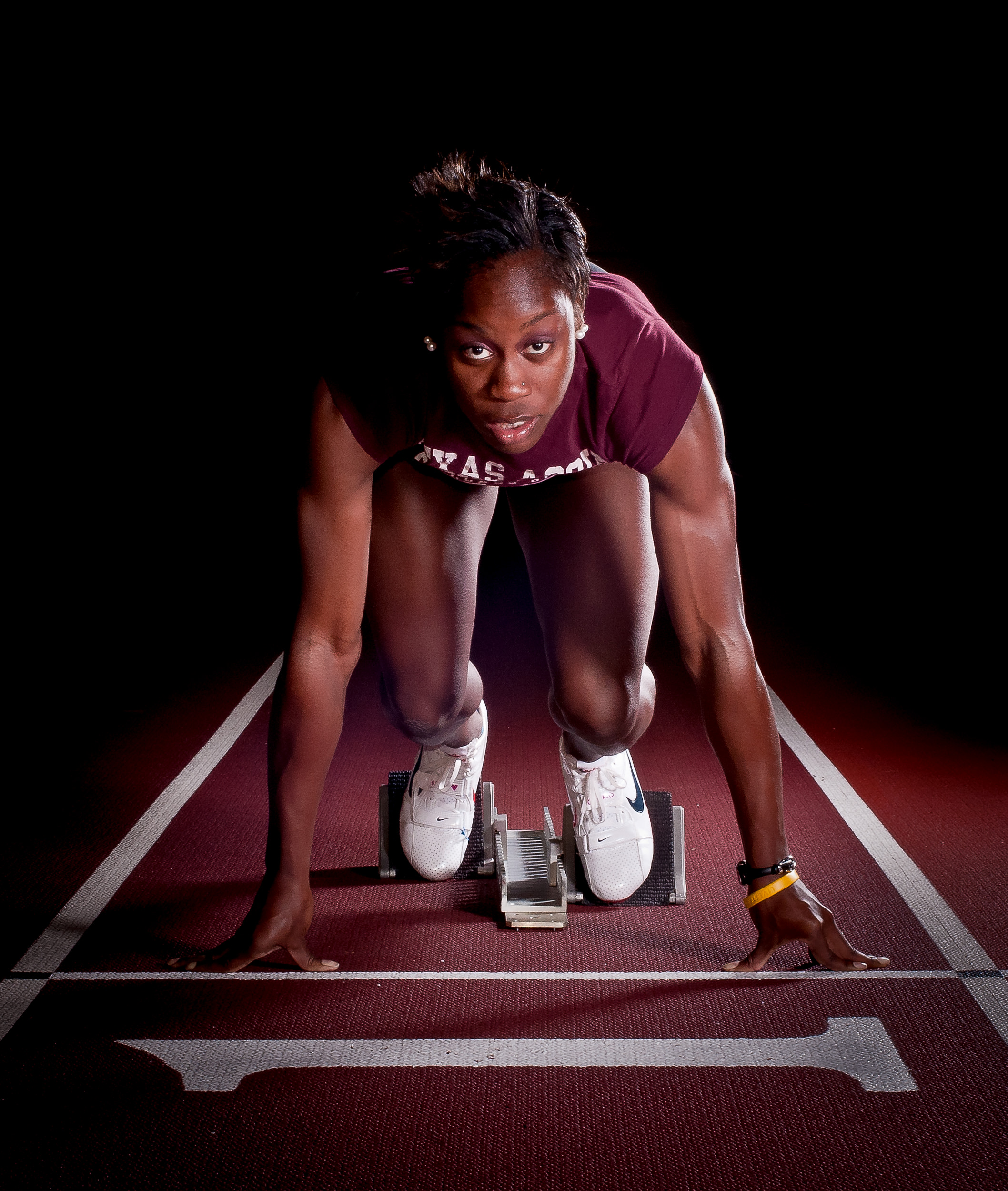 """Senior Jessica Beard, medalist sprinter in the 4x400m at the 2009 Olympics, takes her mark on the starting block, Feb. 1, 2011. As a graduating senior on the Texas A&M University Track & Field team, Beard was named as the Distinguished Letterman of the Year for exhibiting """"honor in all areas""""."""