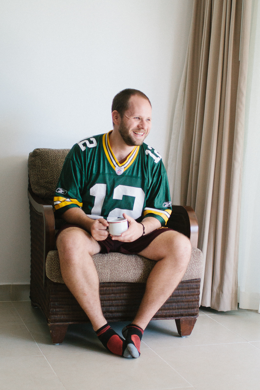 Punta Cana destination wedding, groom wearing football jersey casually drinking coffee