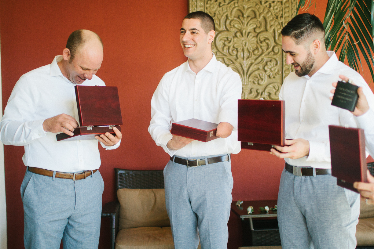 Punta Cana destination wedding, groomsmen open their wedding gifts with excitement