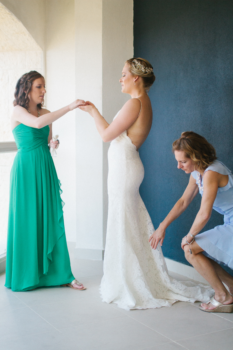 Punta Cana destination wedding, mother of the bride and maid of honor help bride with her wedding gown