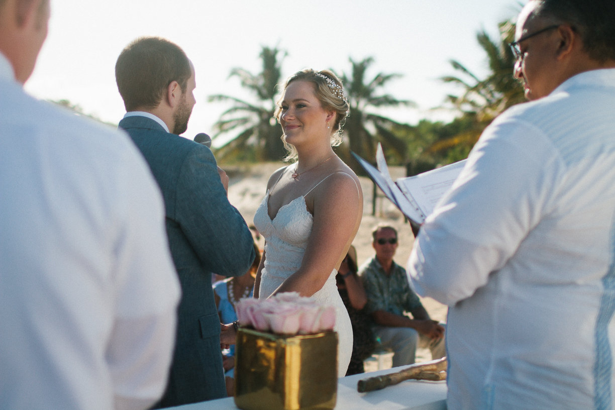 Punta Cana destination wedding, beach front wedding ceremony at sunset, bride begins reading her vows