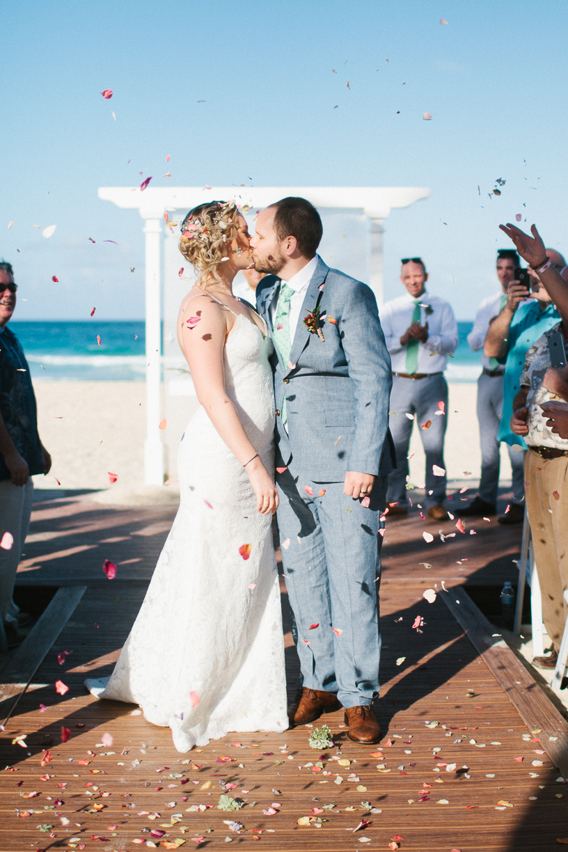 Punta Cana destination wedding, beach front wedding ceremony at sunset, bride and groom celebrate with a kiss