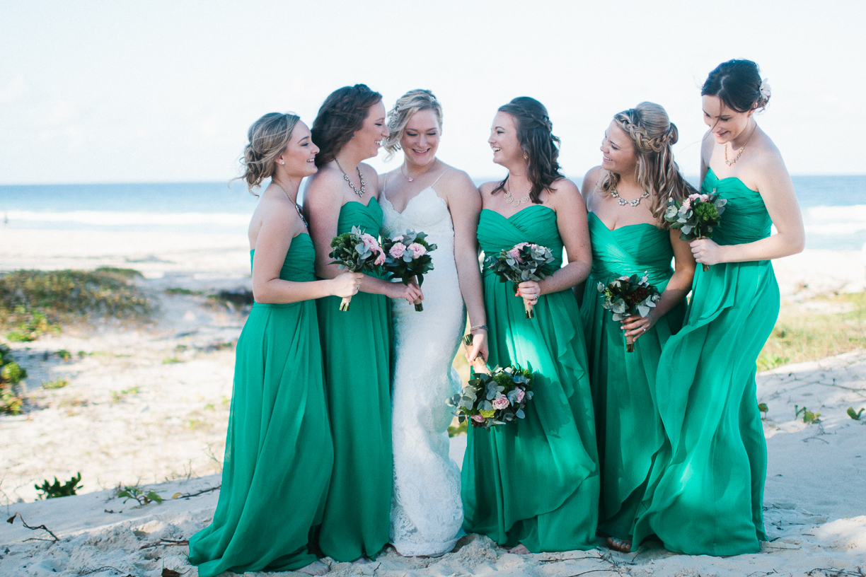 Punta Cana destination wedding, beach front wedding ceremony at sunset, bride smiles with her bridesmaids after the ceremony