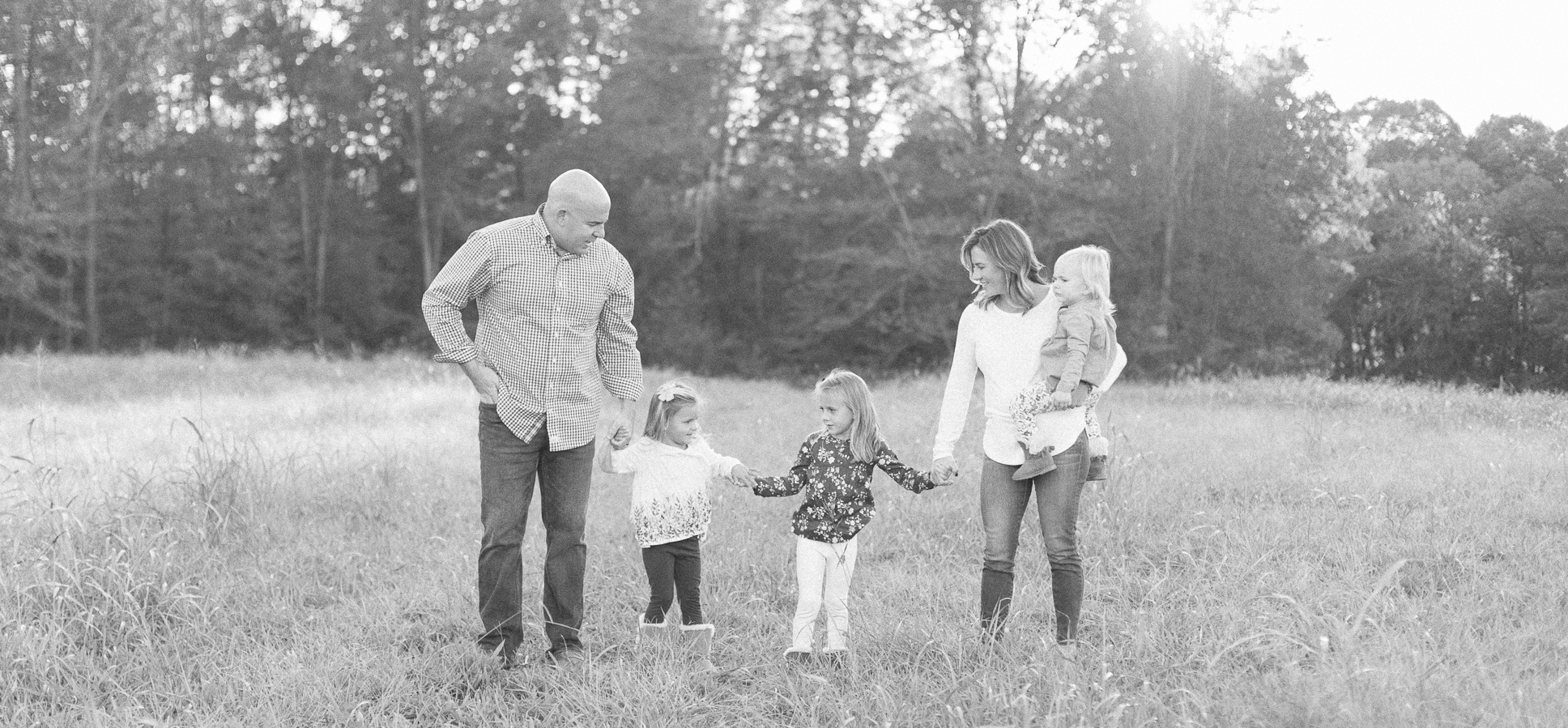 Family of four walking through field Danielle Gallo Photography Charlotte NC.jpg