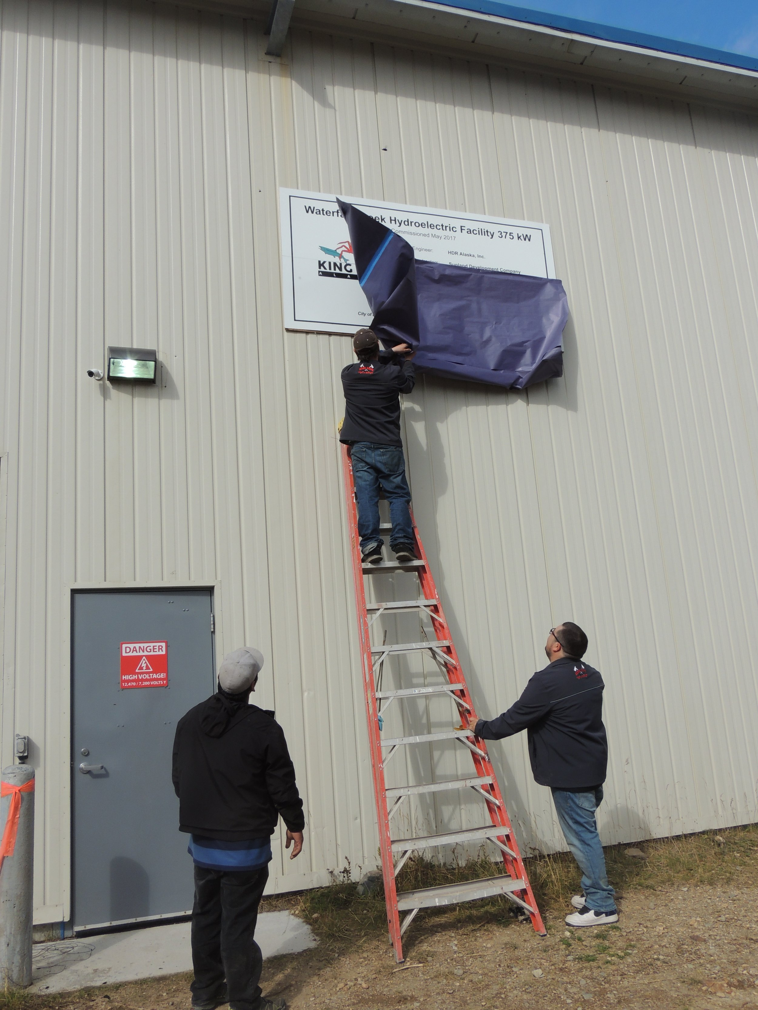 City employees unveiling the new sign at the facility for Waterfall Creek Hydroelectric Facility. Photo provided by Aleutians East Borough.