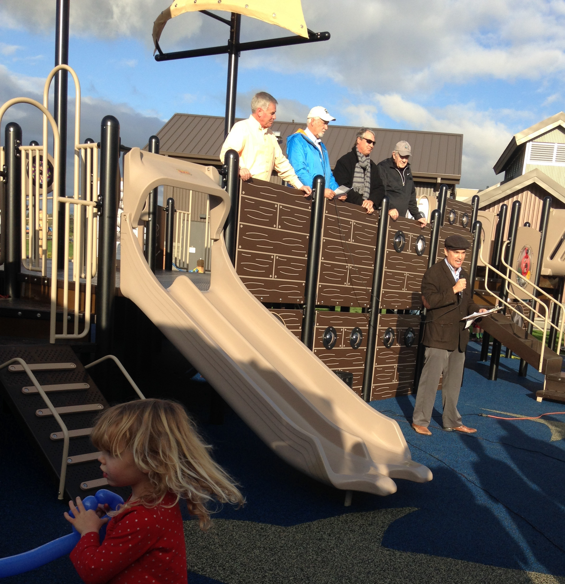 Alex Wenger, AICP talks at the grand opening of the Marine Park Playground. Standing on the Pirate Ship behind him, are from left to right: Ted Morris, Park District Executive Director; Dave Wilbrecht, City Manager (City of Blaine); Jeff Carrington, Park District Commissioner; and Harry Robinson, City of Blaine Mayor. Running in the corner is Alex's daughter Claire.
