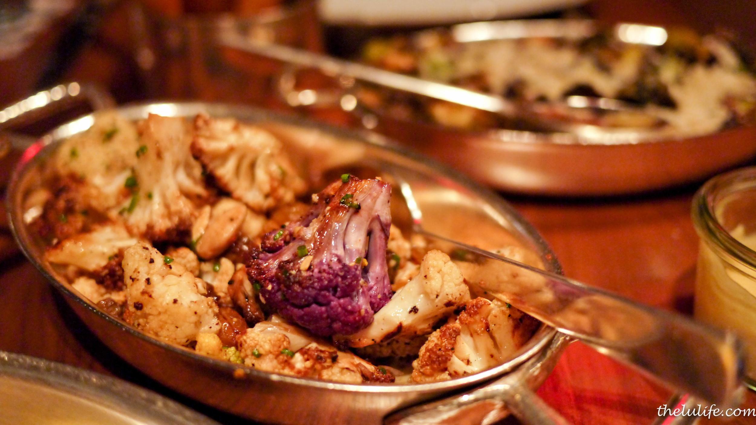 Foreground: Roasted cauliflower (with cheddar fondue, golden raisins, almonds)  Background: Crispy brussels sprouts (lemon, caper, pecorino)