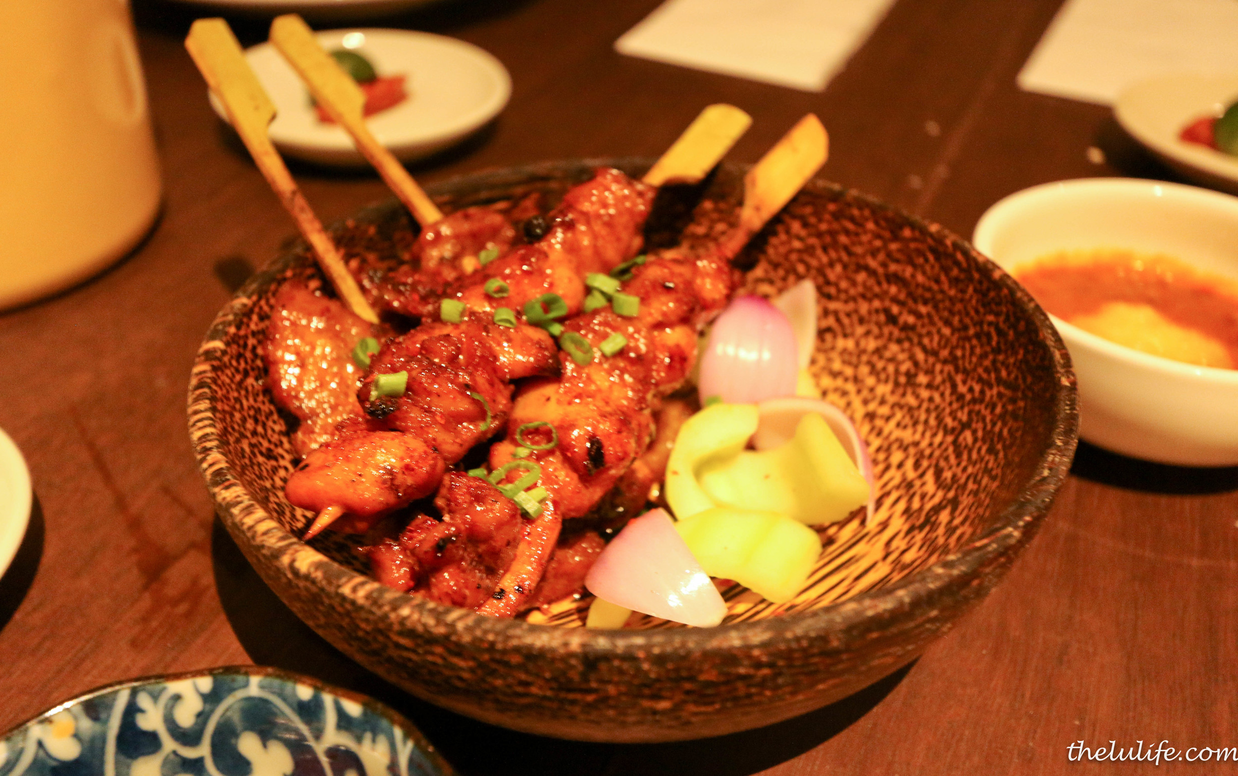 Candlenut Satay - grilled spiced marinated chicken thigh and pork belly served with rich homemade pineapple peanut sauce, cucumbers and red onions