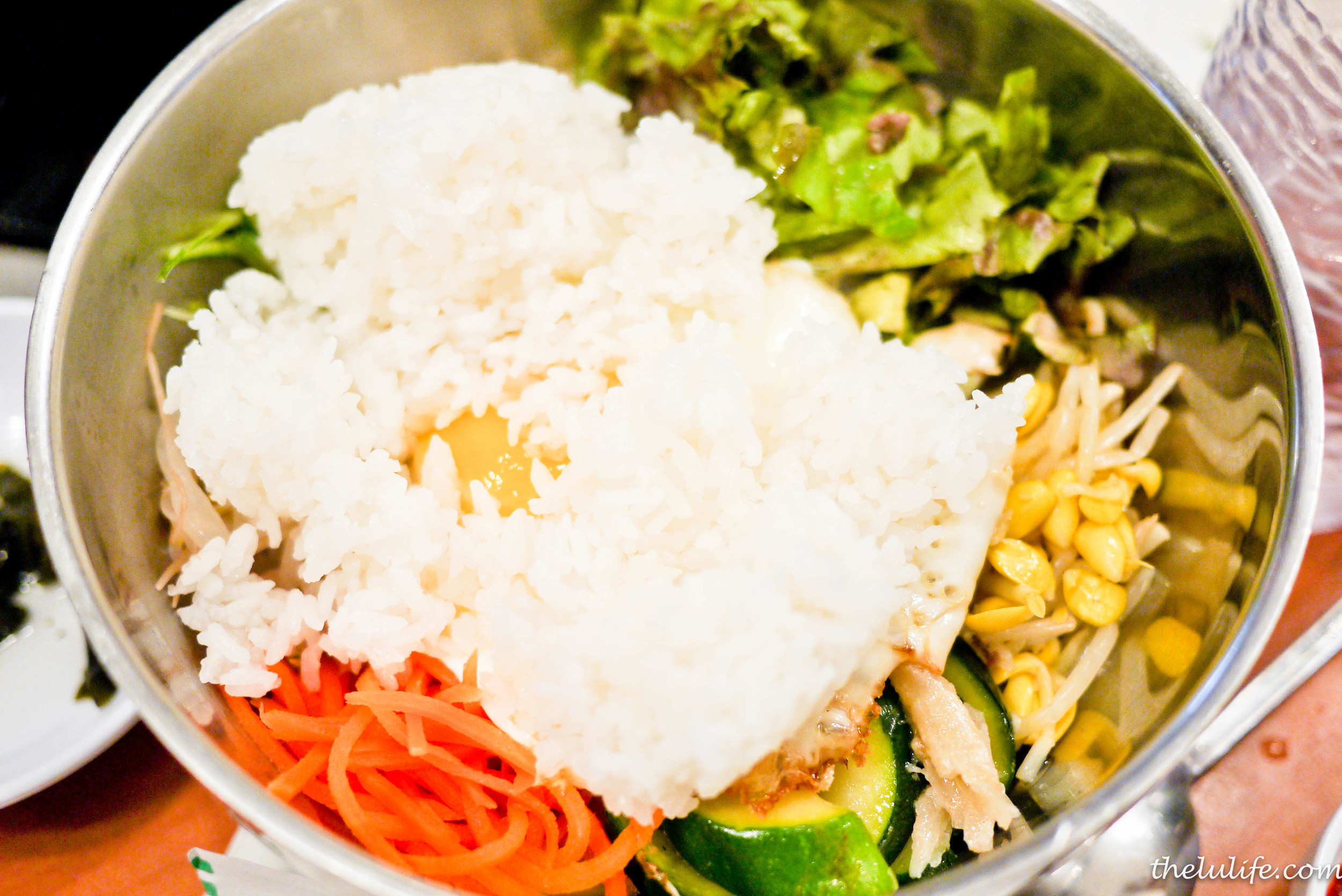 BiBimBap - steamed rice mixed with beef, assorted vegetables, fried egg and side of hot sauce