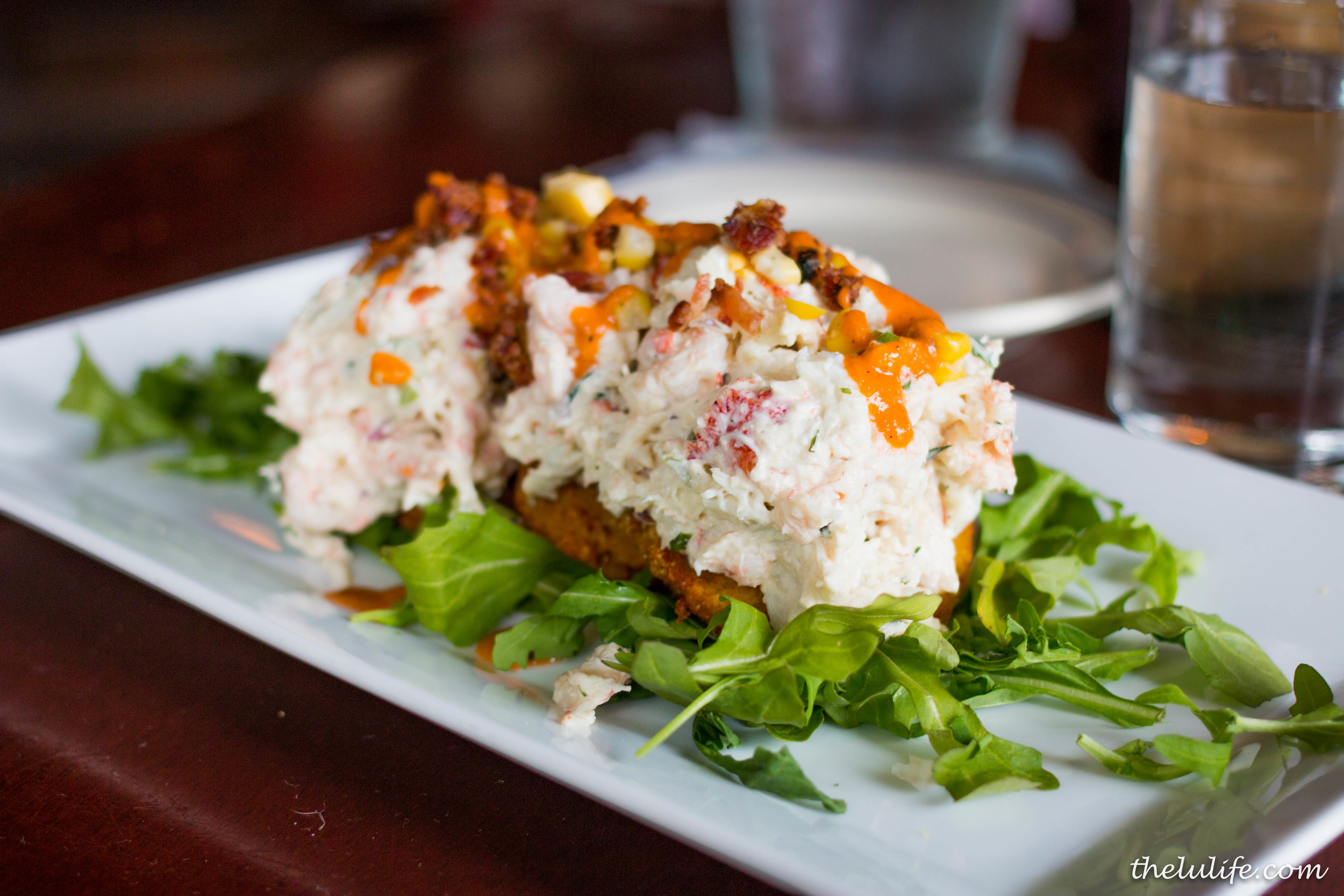 The Sea BLT - Lobster, shrimp, crab salad and corn over fried green tomatoes and topped with bacon and smoked tomato vinaigrette